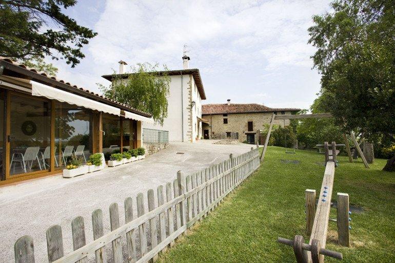 Casa rural Loretxea, Izkue, en las cercanías de Pamplona. Porche acristalado, zona de juegos infantiles y jardín :: Agroturismo en Navarra